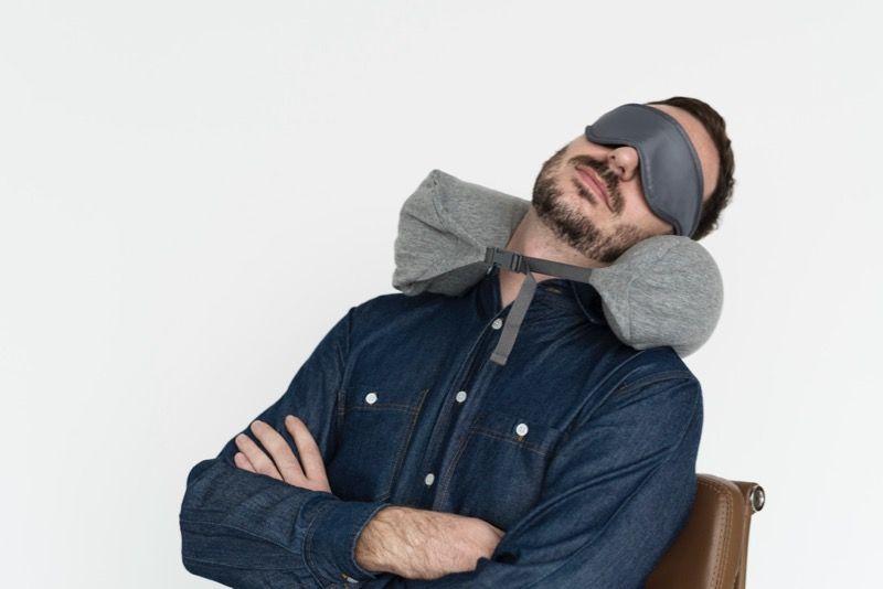 アイマスク(スリープマスク)と無印のネックピローを着けて眠る男性